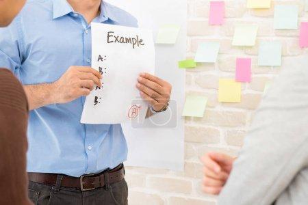Photo pour Enseignant montrant un exemple de papier aux élèves tout en faisant du travail de groupe en classe - concept d'éducation - image libre de droit