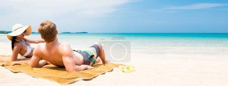 Photo pour Couple allongé sur une plage de sable blanc se détendre et prendre un bain de soleil en été - bannière web panoramique avec espace de copie - image libre de droit