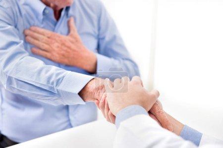 Photo pour Médecin tenant la main masculine senior patient avec des soins - image libre de droit