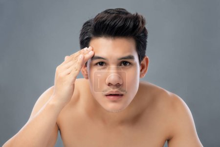 Photo for Portrait of shirtless young handsome Asian man checking his face for skin care and beauty concepts, studio shot isolated on gray background - Royalty Free Image