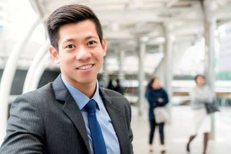Photo for Cheerful handsome Asian Chinese businessman wearing gray suit and blue tie at outdoors covered walkway in the city - Royalty Free Image