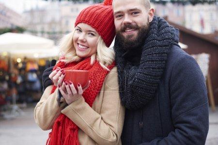 Couple having hot coffee outdoors