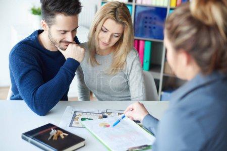 Photo pour Jeune couple dans le bureau de vente interagissant avec la femme et regardant sur les diagrammes - image libre de droit