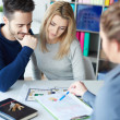Young couple in sales office interacting with woman and looking on diagrams