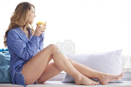 Photo pour Belle jeune femme en pyjama, boire du jus pour le petit déjeuner - image libre de droit