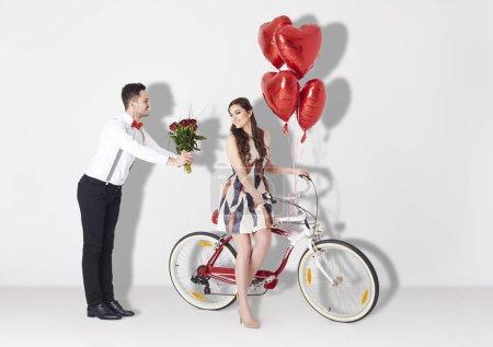 Photo pour Couple heureux avec cadeaux et vélo dans le studio - image libre de droit