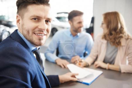Couple and car salesman in shop