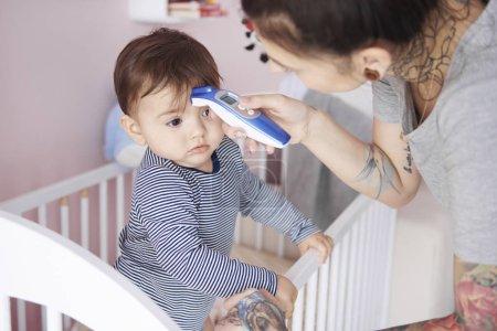 Photo pour Mère avec thermomètre numérique vérifiant la température - image libre de droit