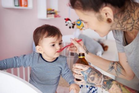 Mother giving baby medicine