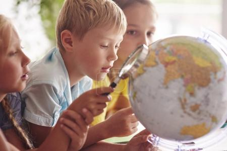 Children using magnifying glass and globe