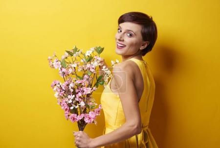 Photo pour Jeune belle femme debout avec bouquet de fleurs sur fond jaune - image libre de droit