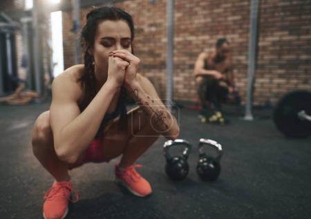 meditating young woman sitting at gym
