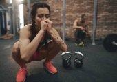 meditating young woman sitting at gym