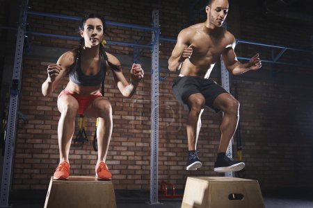 sporty couple jumping on platforms at gym
