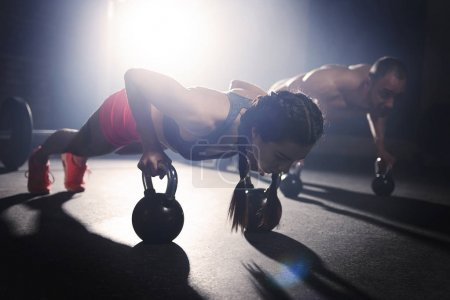 couple doing push ups with dumbbells