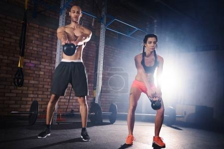Sporty couple training with dumbbells at gym