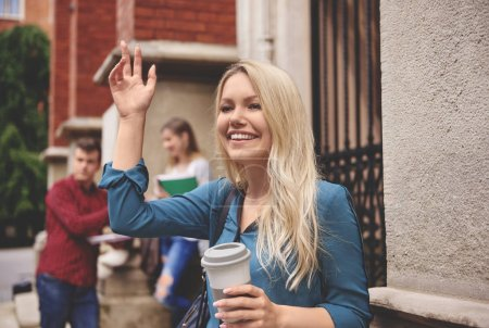 Student girl holding paper cup of coffee and wavin...