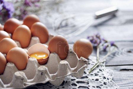 Broken egg among brown eggs in egg box