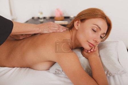 Photo pour Magnifique femme sexy bénéficiant d'un massage relaxant par un thérapeute spa professionnel, copier l'espace. Une belle femme se fait masser - image libre de droit