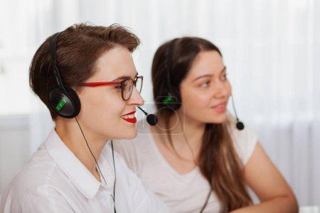 """Photo pour Deux jeunes femmes joyeuses portant des casques d """"écoute et travaillant au centre d'appels. Les employés du service à la clientèle aident les clients en ligne en utilisant des écouteurs avec microphones - image libre de droit"""