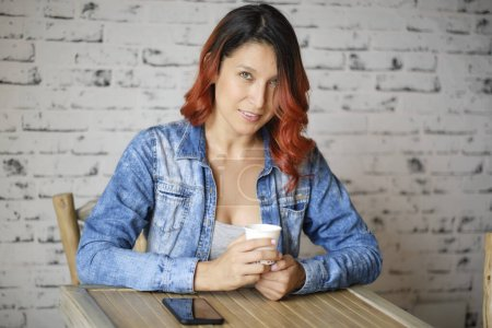 Photo for Woman holds a white cup while looking at the camera. Latin woman with red hair and jean jacket. On the table his phone. White background - Royalty Free Image