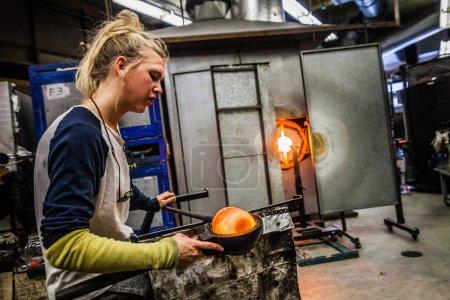 Photo pour Atelier de soufflage de verre - Deux femmes façonnant le verre sur la pipe - image libre de droit