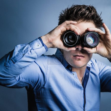 Photographer Looking Through Lenses in Studio