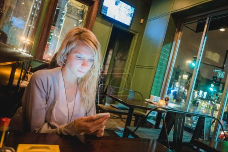 Montreal, Canada - November 30, 2017: Woman in a Restaurant Checking for an Address on a Smartphone with St-Denis Street, Montreal in Background at Night.