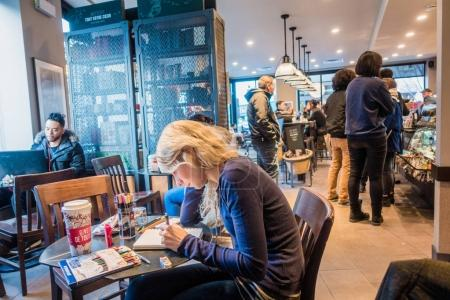Montreal, Canada - December 1, 2017: Young Woman Sketching on a Paper Pad in a Montreal Starbucks.