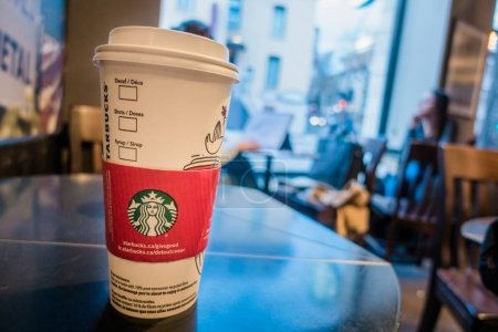 Montreal, Canada - December 1, 2017: Starbucks Coffee Cup on a Table with Blurred People in Background.