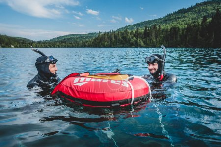 GASPESIE, CANADA - JULY 20, 2017: Freediver Couple Talking together at the Buoy and Getting Ready for the next Dive