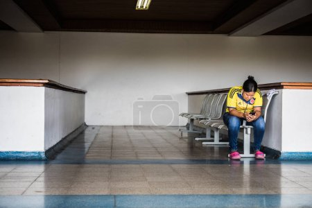 SAN ANDRES ISLAND, Colombia - Circa March 2017: Colombian Woman Wearing the Country Soccer Shirt at the San Andres Airport... Waiting.