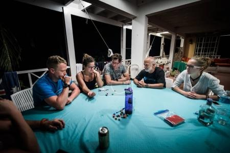 SAN ANDRES ISLAND, Colombia - Circa March 2017: Group of Adults playing Yum Dice Game at Night on the Balcony.