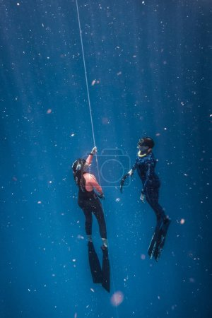 SAN ANDRES ISLAND, Colombia - Circa March 2017: Freediver and his Safety Diver Diving and Following the Life Line at all time in the Deep Blue of San Andres Island, Colombia.