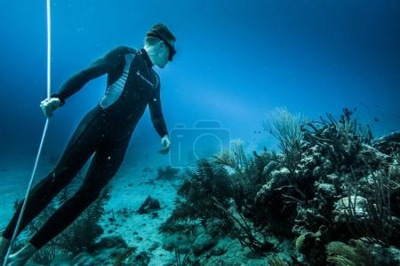 SAN ANDRES ISLAND, Colombia - Circa March 2017: Freediver at the Bottom of the line Looking at the Corals and doing a Breath Holding