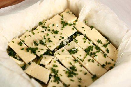 Photo pour Saupoudrer la couche de fromage d'ail haché. Making Potato and Leek Filo Pie. Série. - image libre de droit
