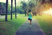asian woman running at tropical park