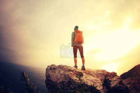 Photo for Successful hiker standing on seaside mountain peak - Royalty Free Image