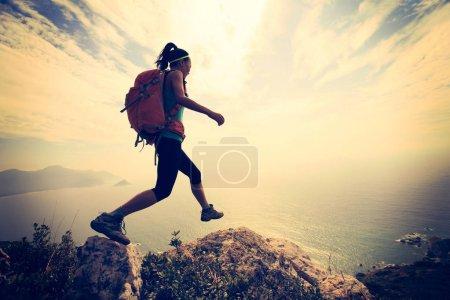 hiker climbing on mountain peak