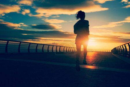 Photo for Young fitness woman running at seaside during sunset - Royalty Free Image