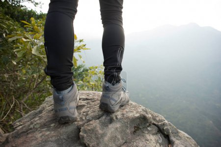Photo for Female hiker standing on mountain top - Royalty Free Image