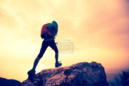 Photo for Successful hiker climbing on seaside mountain peak - Royalty Free Image
