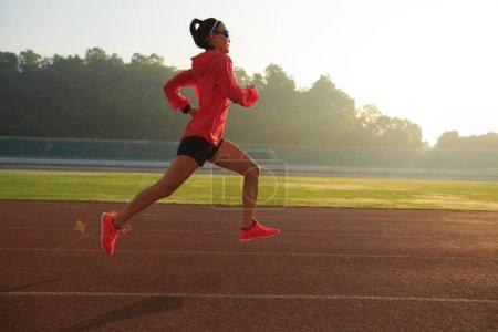 Young woman running on stadium