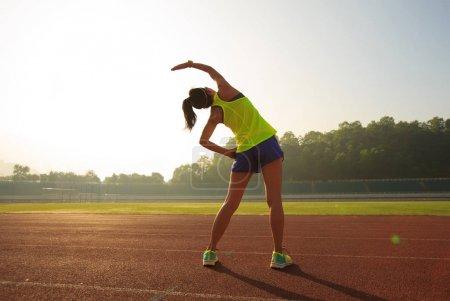 Photo pour Jeune femme étirant pendant la matinée ensoleillée sur le stade - image libre de droit