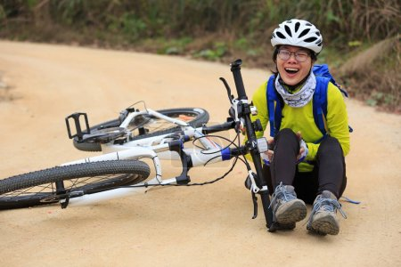 Photo for Female cyclist getting injured after falling from mountain bike on road - Royalty Free Image