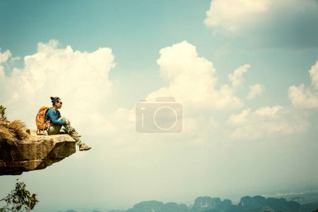 Photo for Young woman sitting on cliff and enjoying  the view - Royalty Free Image