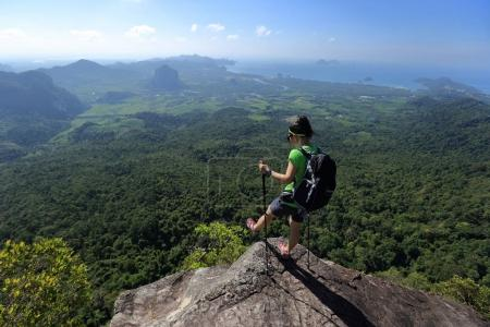 Foto de Joven mochilera disfrutando de la vista desde el pico de la montaña - Imagen libre de derechos