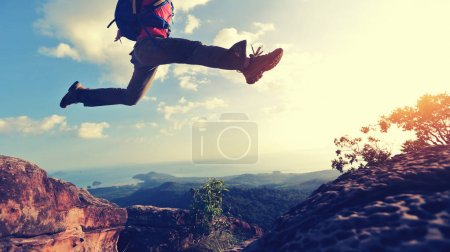 Photo for Cropped image of young woman hiker jumping on mountain peak - Royalty Free Image