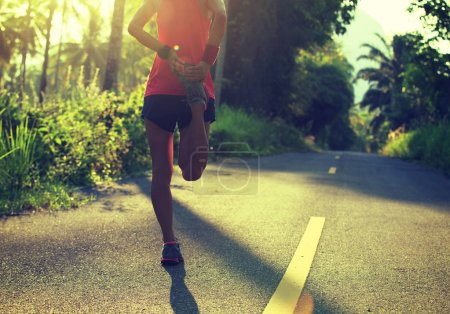 Young female runner stretching legs