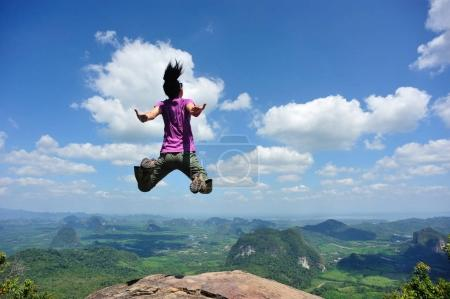 Young woman jumping on mountain peak